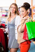 pic of boutique  - Asian and Caucasian Women friends shopping in boutique or fashion store - JPG