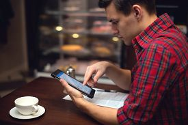 stock photo of cafe  - Young  man drinking coffee or tea in the city cafe during lunch time and working on tablet - JPG