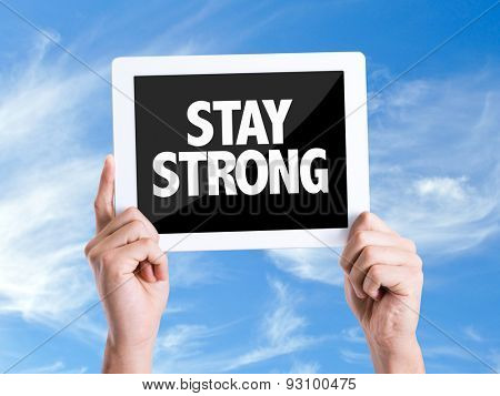 Tablet pc with text Stay Strong with sky background