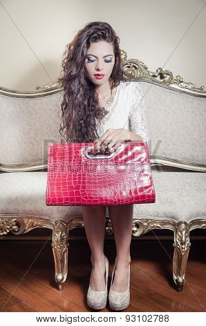 Pretty model girl sitting on victorian sofa posing for camera