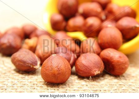 Hazelnut Pouring Out Of Yellow Cup On Jute Canvas