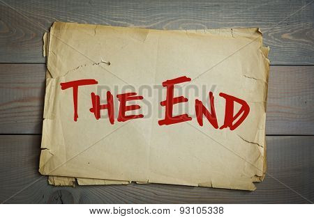 The End. Old paper on a wooden background
