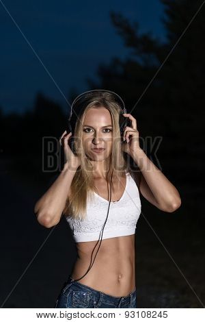 blond girl with  headphones outdoor posing