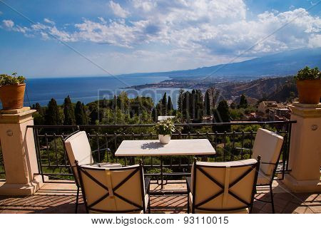 table and chairs at balcony overlooking sicilian coastline