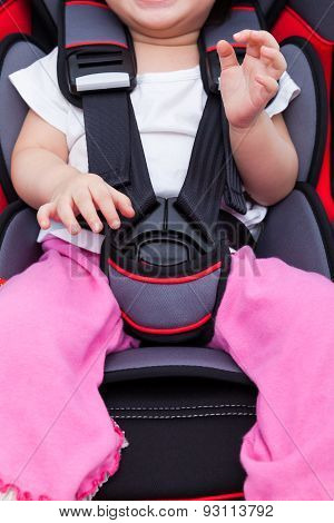 Girl Sitting At Carseat And Fasten Seat Belt