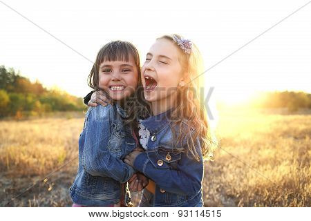 Two Cheerful Friends Snuggling Outdoors In The Park