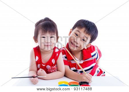 Children Looking At The Camera And Smiling, Holding A Paintbrush. Isolated On White