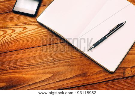 table with notebook, smartphone and pen