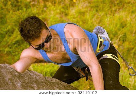 man climbing mountain with sunglasses