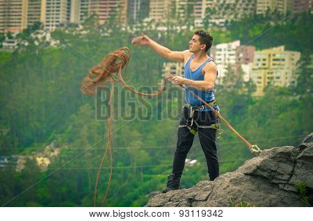 athletic man standing on cliff with rope in hands