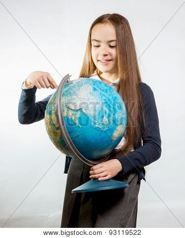 Cute Smiling Girl Pointing At Earth Globe Against White Background