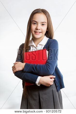 Smiling Schoolgirl Posing With Red Book Against Isolated Background