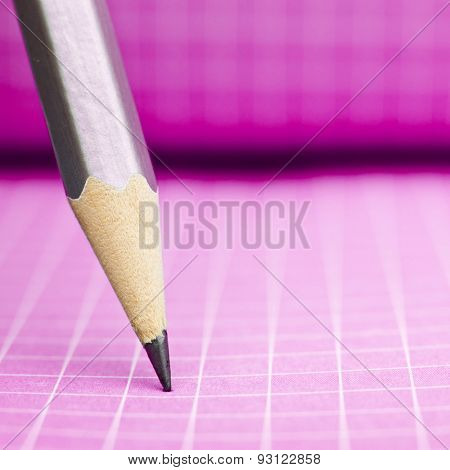 Sharp wooden pencil on pink checkered paper