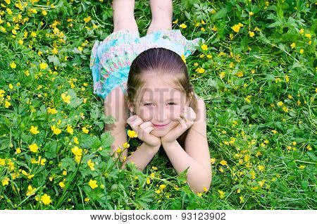 The Girl Lies On A Glade With Flowers