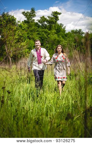 Traditional Ukrainian Couple Holding Hands And Walking At Field