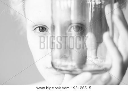 Close-up portrait of curly girl looks through the empty glass. Black and white photography.
