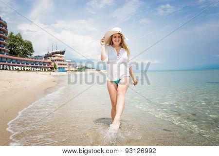 Happy Woman In White Hat Walking On The Seashore