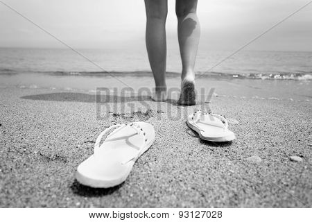 Black And White Closeup Photo Of Woman Walking Into The Sea Water