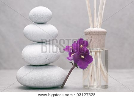 stack of pebble stones beside african violet flower and bottle with fragrance sticks