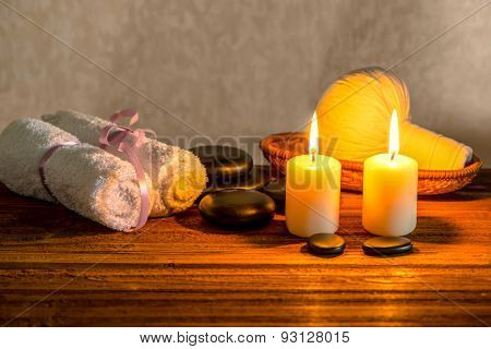 Spa Still Life Of White Towels, Candles, Thai Herbal Compress Balls In Basket And Zen Basalt Stones