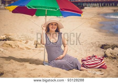 Toned Photo Of Cute Pregnant Woman In Striped Dress On Beach