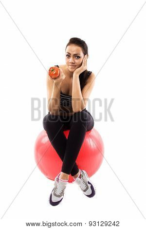 Girl Is Sitting On The Fitness Ball And Holding A Tomato