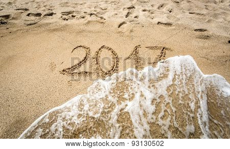 Closeup Of 2017 Written On Sand Being Washed Off By Wave