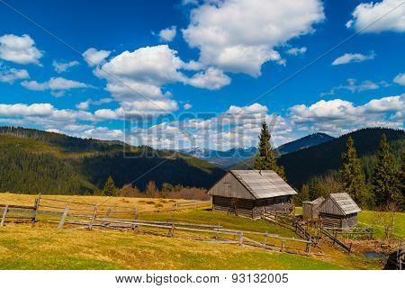 Mountain Landscape With Two Wooden Houses .