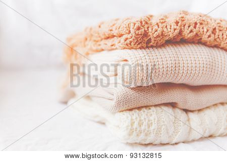 Pile Of Beige Woolen Clothes On A White Background. Warm Knitted Sweaters And Scarfs Are Folded In O