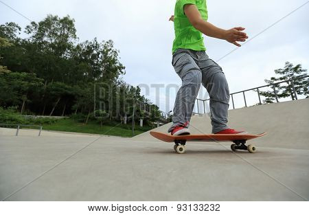 skateboarder legs riding skateboard at skatepark