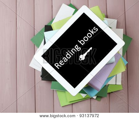 PC tablet on pile of books and magazines on wooden background