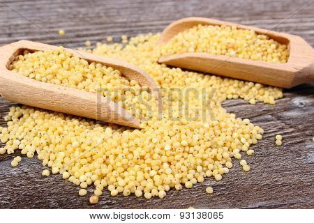 Heap Of Millet Groats With Spoon On Wooden Background