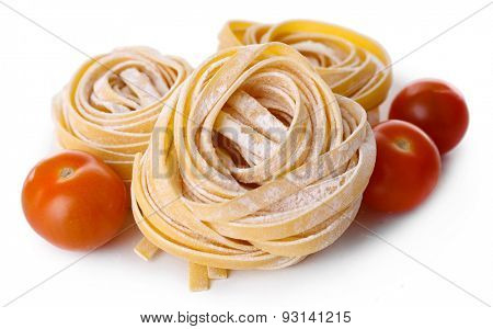 Pasta tagliatelle nests with cherry tomatoes isolated on white