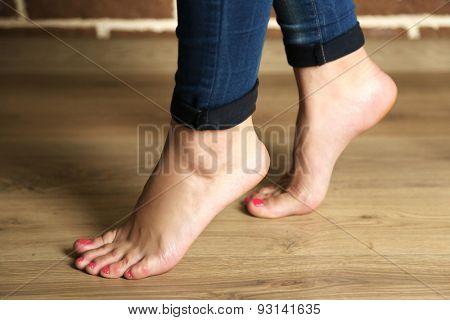 Beautiful female legs on wooden floor background