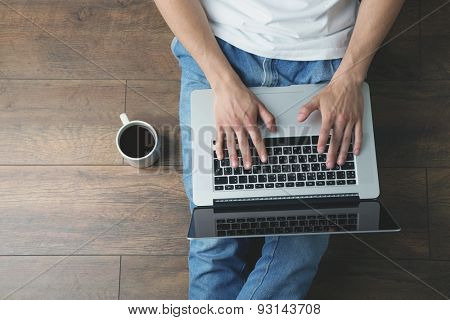 Young man sitting on floor with laptop and cup of coffee in room