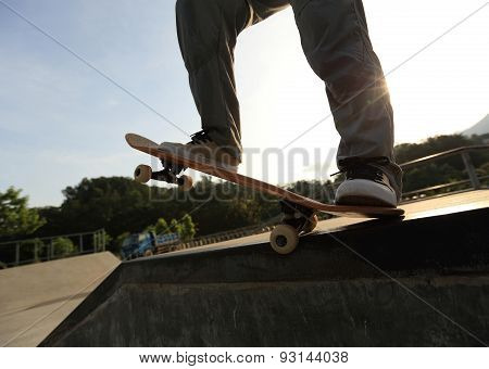 skateboarder legs riding skateboard at sunrise  skatepark