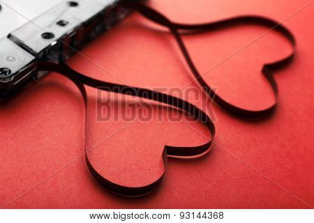 Audio cassette with magnetic tape in shape of hearts on red background
