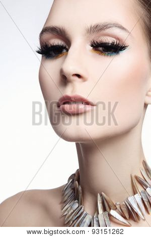 Portrait of young beautiful slim woman with false eyelashes and fancy necklace