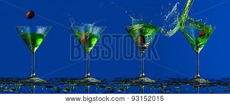 Green water splash in glass and cherry
