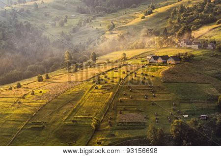 Early summer morning in a small Carpathian village. The first rays of the sun lit slopes