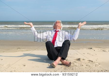 Senior business man sitting in meditation at the beach