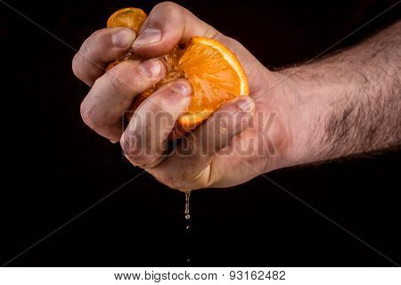 Male hand squeezing orange. Concept of anger and irritation