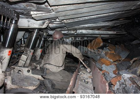 Donetsk, Ukraine - August, 16, 2013: Miner Working In A Confined Space Clears From The Slag Conveyor