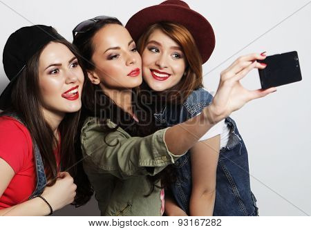 Three stylish sexy hipster girls best friends taking selfie with mobile phone