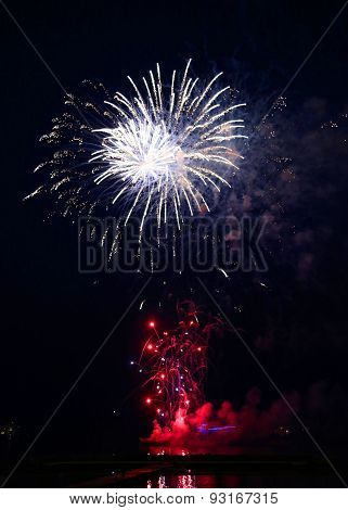 Fireworks of various colors bursting against a black sky background and cruise ship at night