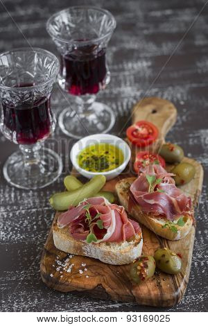 Bruschetta With  Ham, Olives, Cherry Tomatoes In Olive Board And Red Wine On A Dark Wooden Backgroun