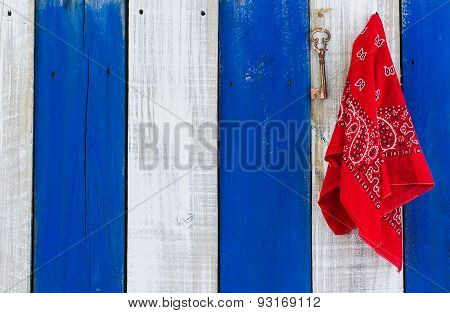 Red bandana and skeleton key hanging on rustic background