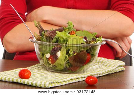 Girl hesitantly eating a leaf of lettuce