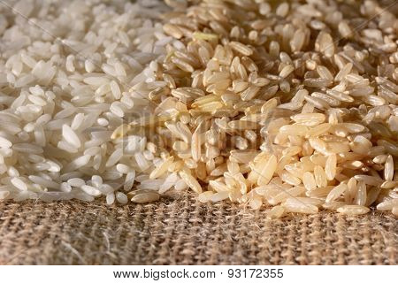 Closeup of white and brown rice on a burlap surface. Warm side light with shallow depth of field.
