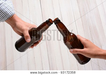 A man and a woman toasting with beer bottles. They are clinking the bottle tops over a rustic wood background.